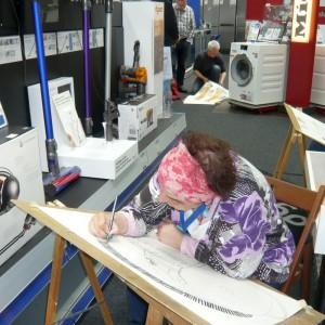Franziska Fiedler zeichnet im Elektrofachgeschäft
